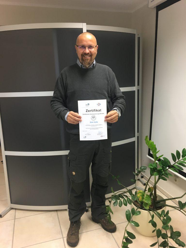 Ein lächelnder Mann mit einem Zertifikat in der Hand